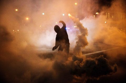 A protester throws a tear gas canister back toward riot police after a 10 p.m. curfew went into effect in the wake of Monday's riots following the funeral for Freddie Gray,  in Baltimore. (AP Photo/David Goldman)