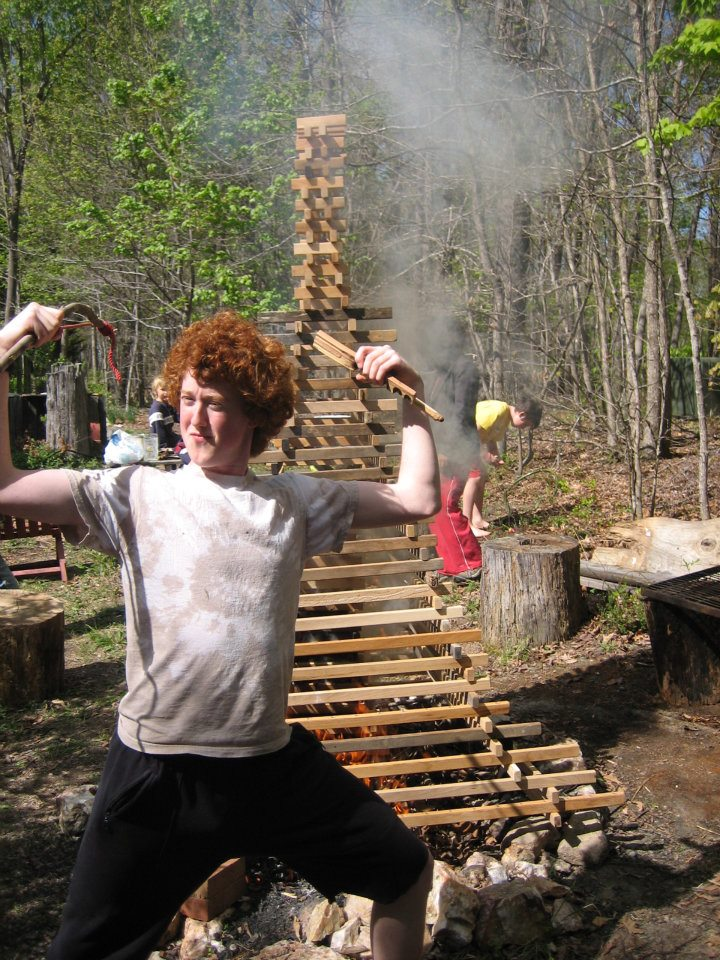 Rowan on his 18th birthday having lit the fire behind him with a bowdrill.
